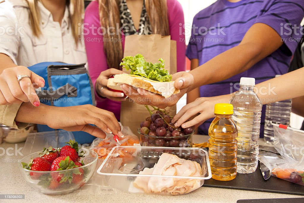 Multi-ethnic group teenagers in kitchen making school lunches. stock photo
