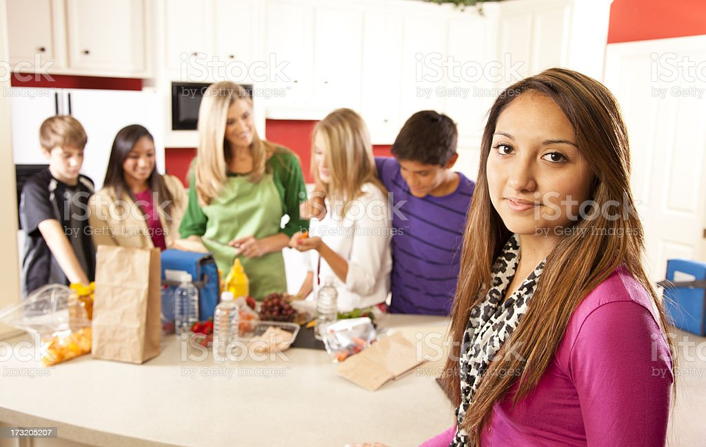 Multi-ethnic group teenagers, mom in kitchen making school lunches. royalty-free stock photo