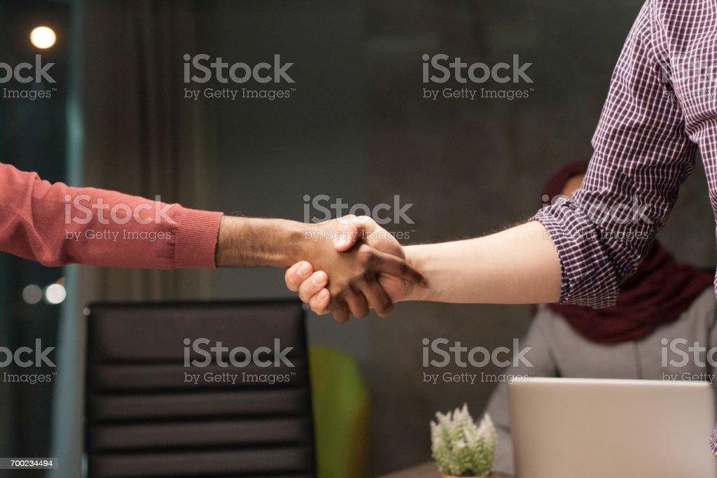 Multiethnic handshake in office at meeting stock photo