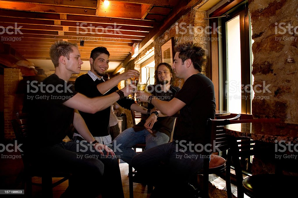 Multi-ethnic men friends at the bar sharing beer, drinks. Cheers! stock photo