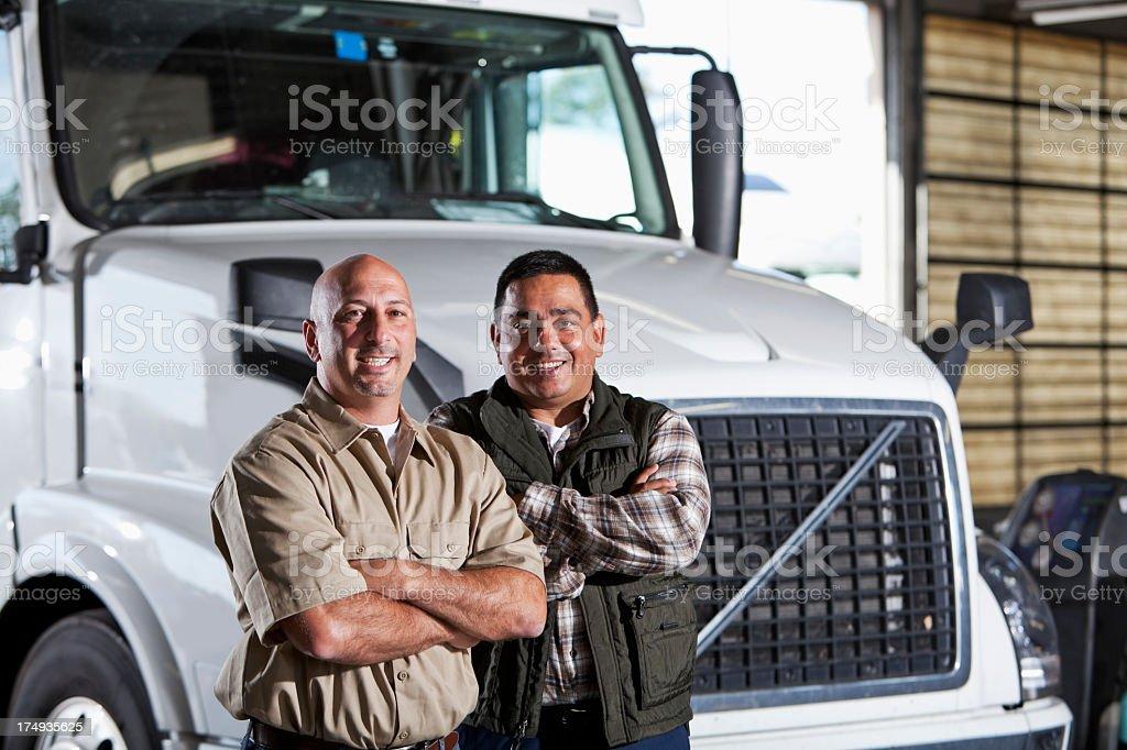 Multi-ethnic men standing next to semi-truck royalty-free stock photo