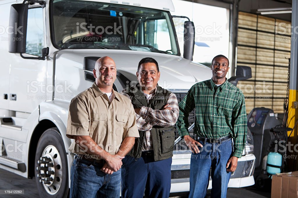 Multi-ethnic men standing next to semi-truck stock photo