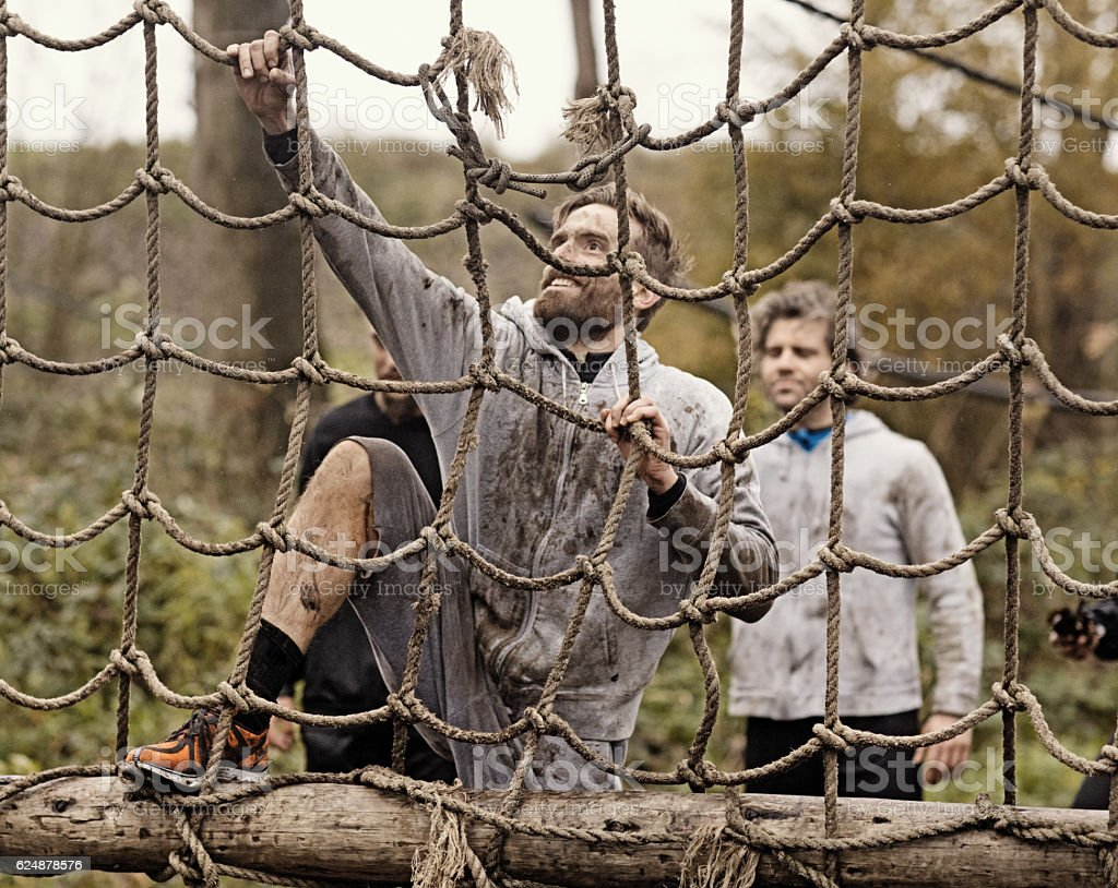 Multiethnic mud run team of men climbing on obstacle course stock photo