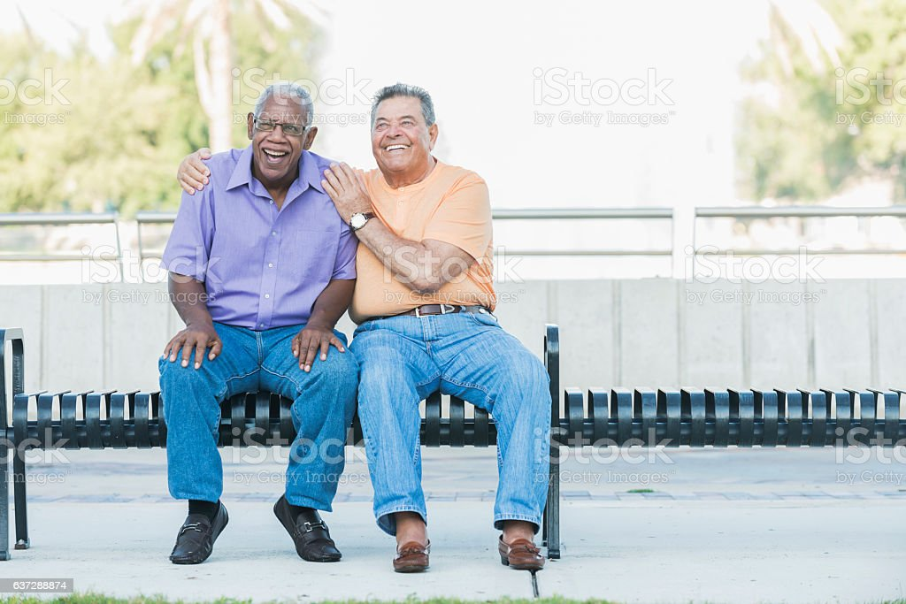 Multi-ethnic senior men hanging out on park bench stock photo