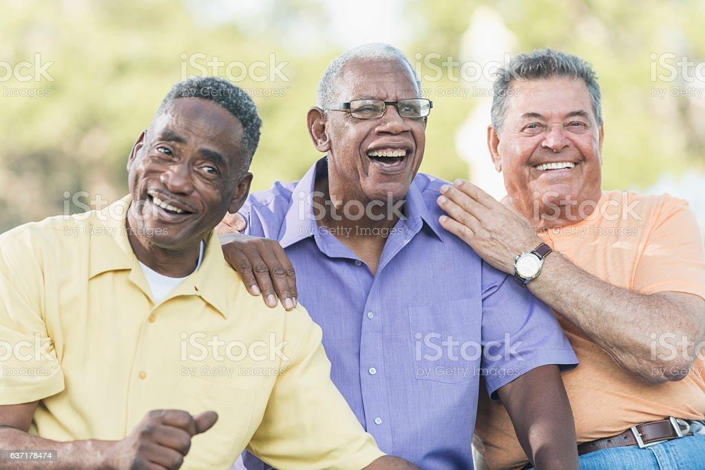 Multi-ethnic senior men on park bench, smiling stock photo