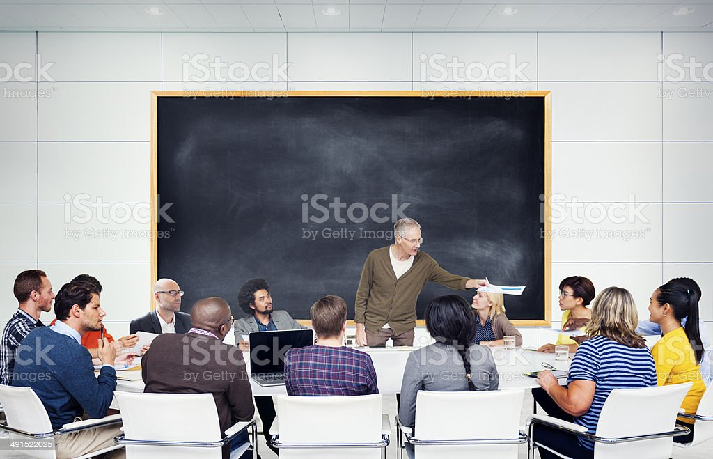 Multi-ethnic students gathered around professor stock photo