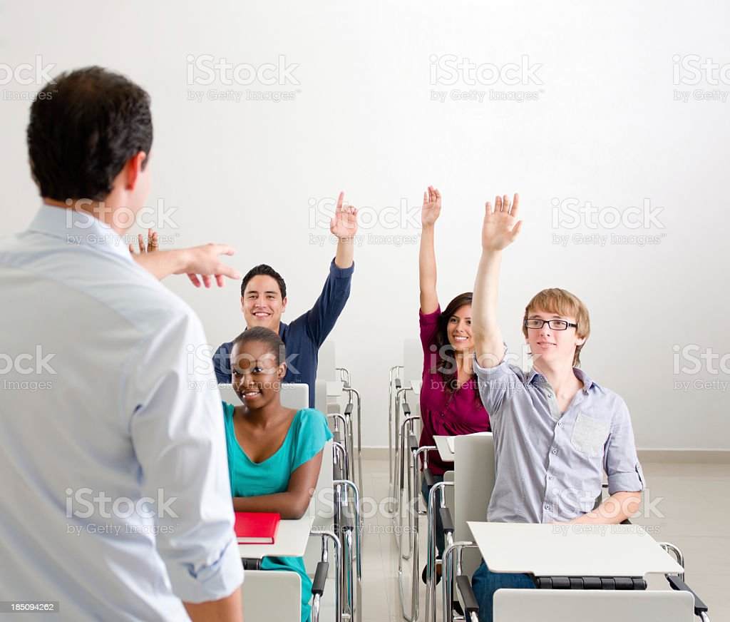 Multi-ethnic students raising hands in class royalty-free stock photo