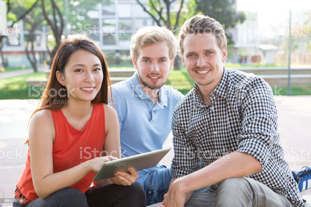 Multi-ethnic students resting in park stock photo