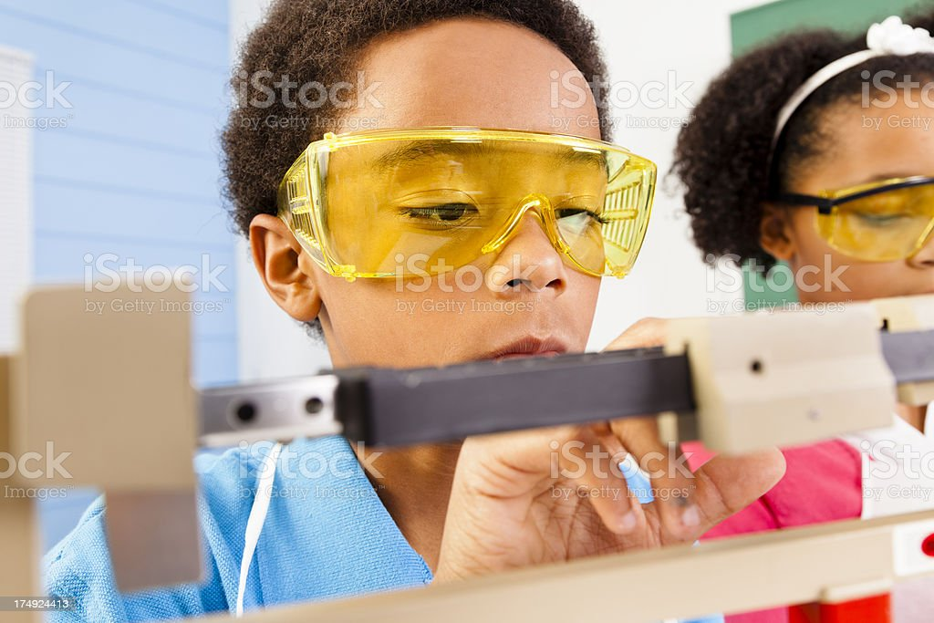 Multi-Ethnic students science lab safety glasses and scale royalty-free stock photo