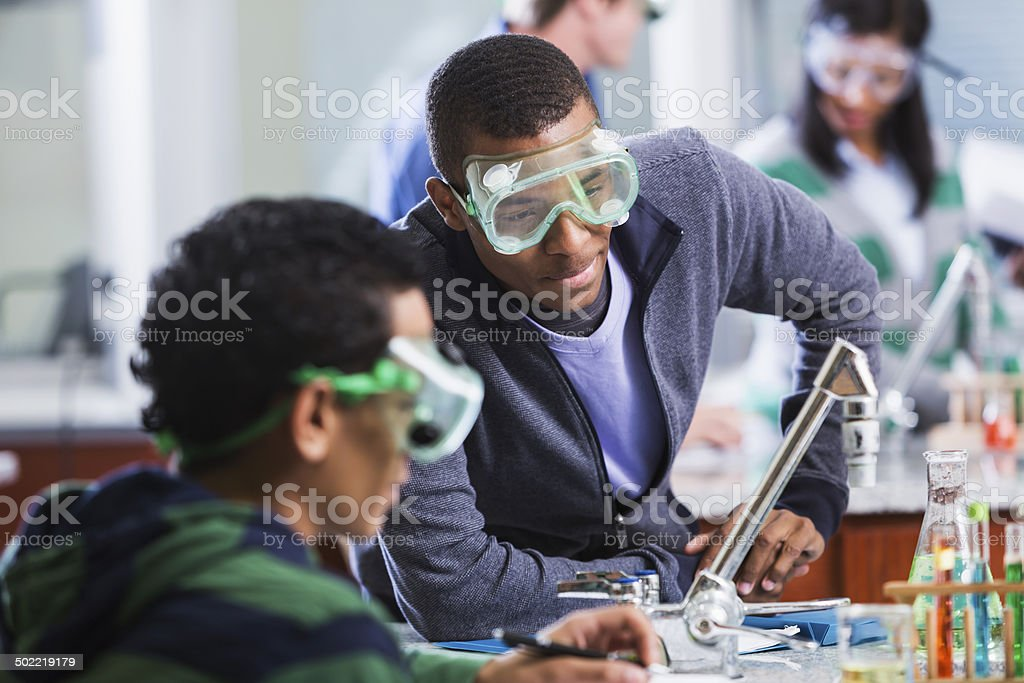 Multi-ethnic students wearing safety glasses in chemistry class stock photo