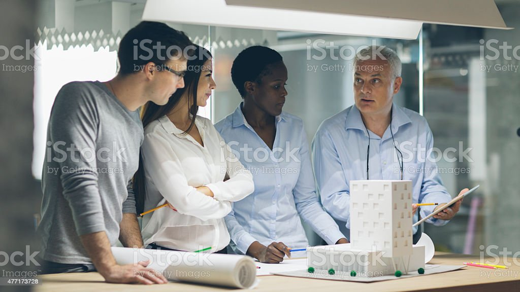 Multiethnic Team of architects reviewing architectural model in the office. stock photo