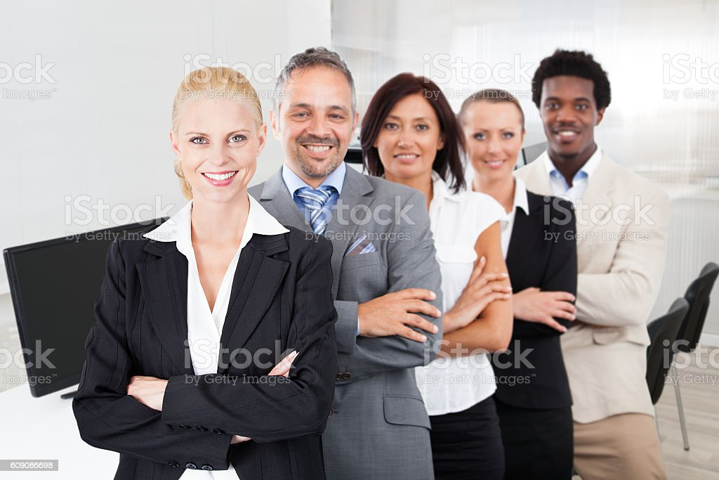 Multiethnic Team With Arms Crossed Smiling In Office stock photo