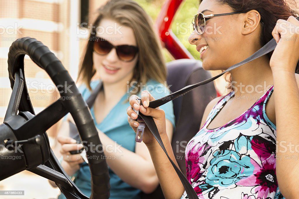 Multi-ethnic teenage girls fasten seat belts before driving vehicle. Safety. stock photo