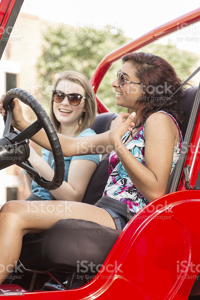 Two pretty, multi-ethnic teen girls happily taking a summer road trip...
