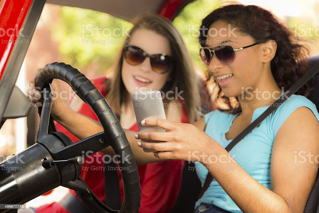 Multi-ethnic teenage girls texting while driving their car. stock photo