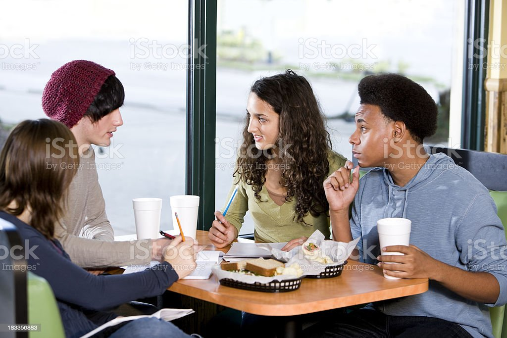 Multi-ethnic teenagers having lunch together in restaurant royalty-free stock photo
