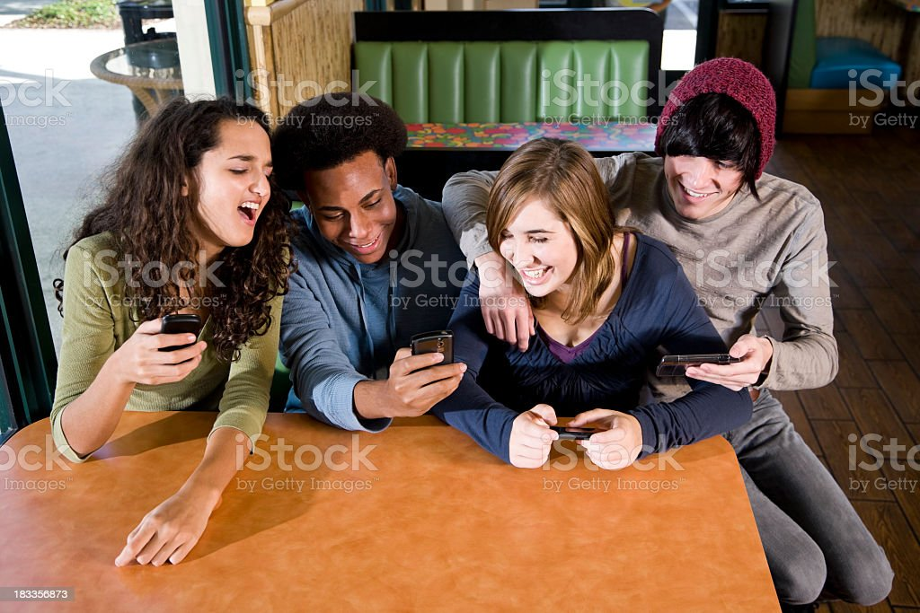 Multi-ethnic teenagers in diner texting on mobile phones stock photo