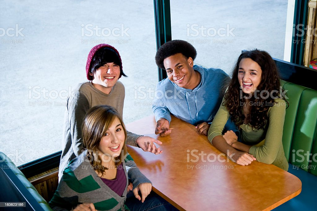Multi-ethnic teenagers sitting together in diner royalty-free stock photo