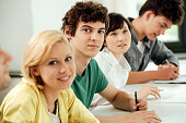 Multi-ethnic university students sitting at table in classroom