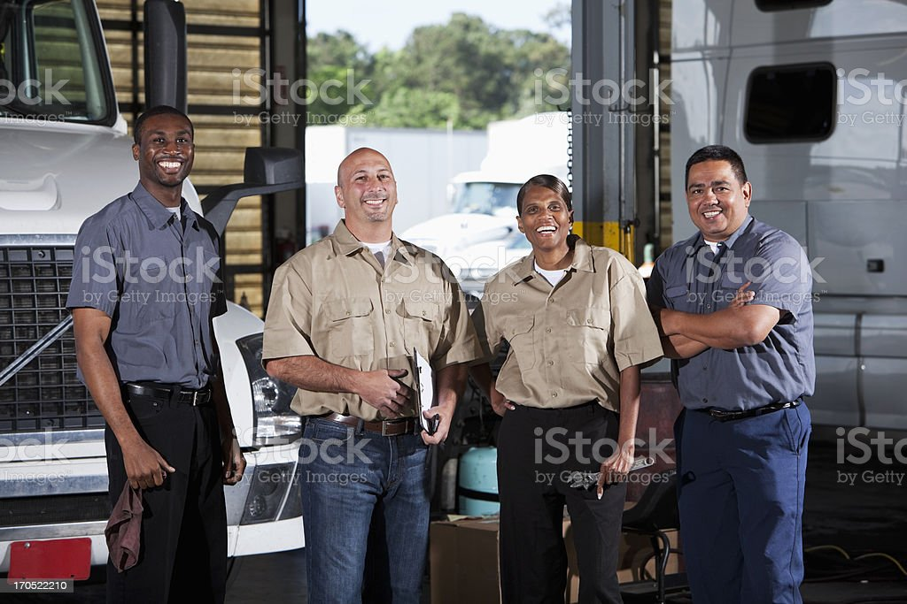 Multi-ethnic workers at trucking facility stock photo
