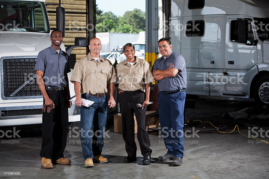 Multi-ethnic workers at trucking facility royalty-free stock photo