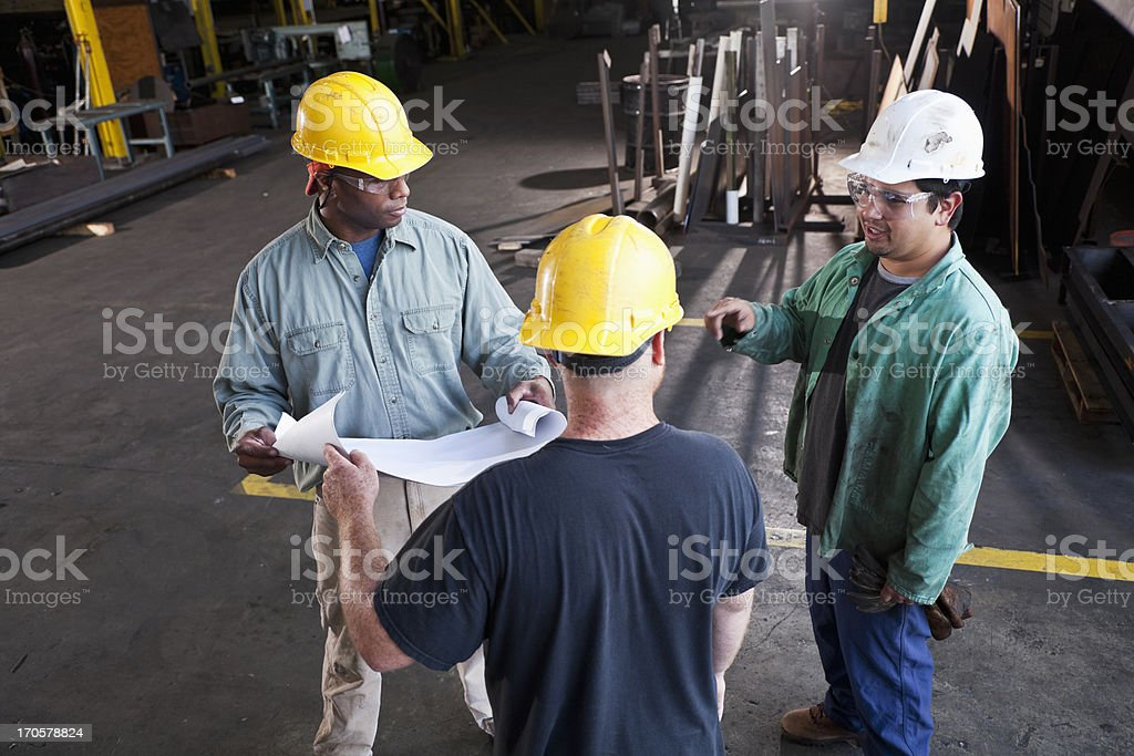Multi-ethnic workers in fabrication shop stock photo