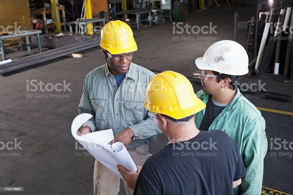 Multi-ethnic workers in fabrication shop royalty-free stock photo