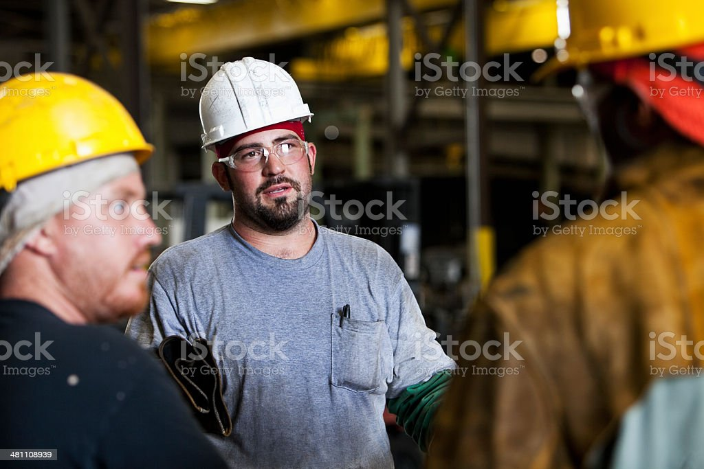 Multi-ethnic workers in fabrication shop talking stock photo