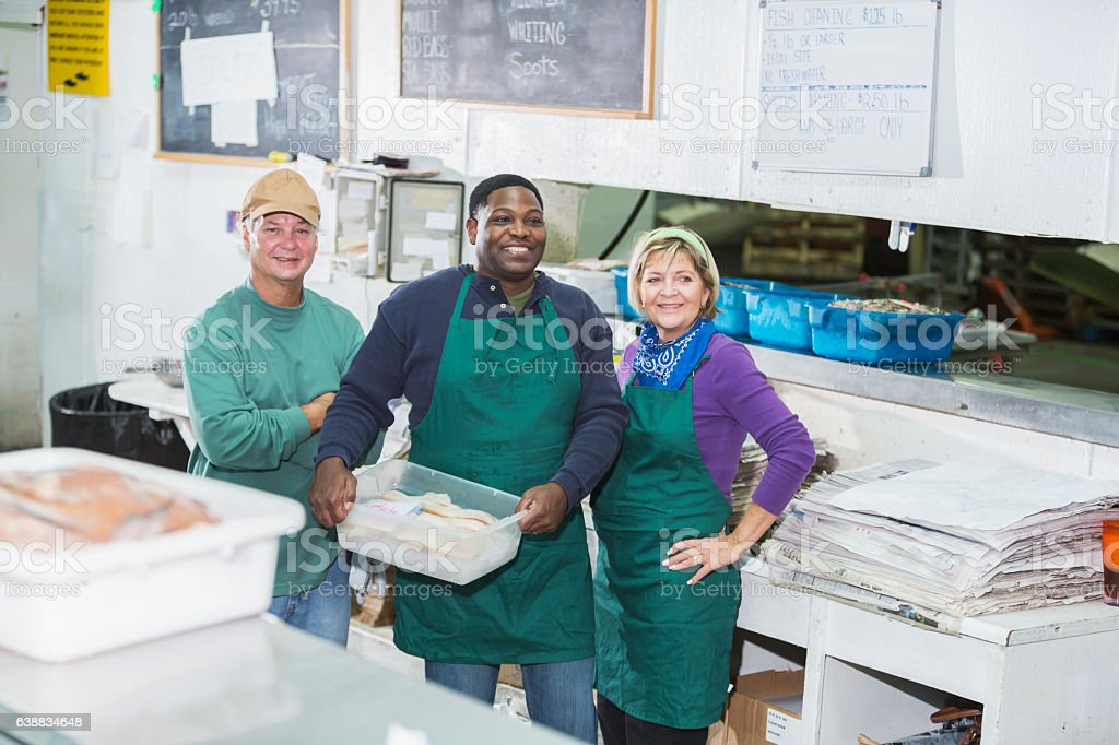 Multi-ethnic workers in seafood store stock photo