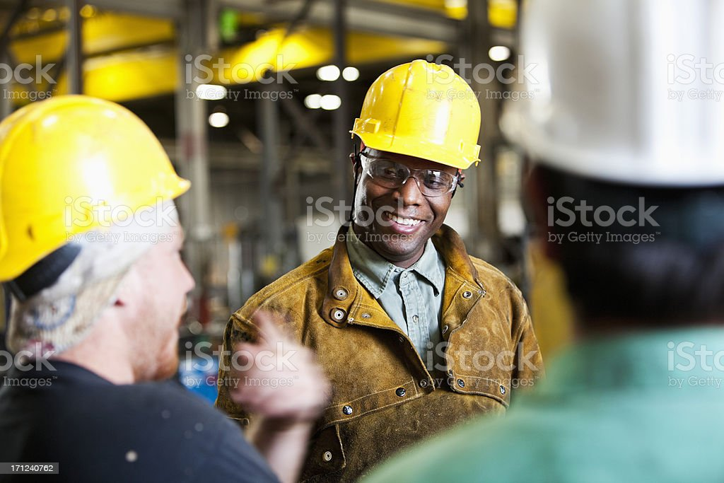 Multi-ethnic workers wearing hard hats, talking stock photo
