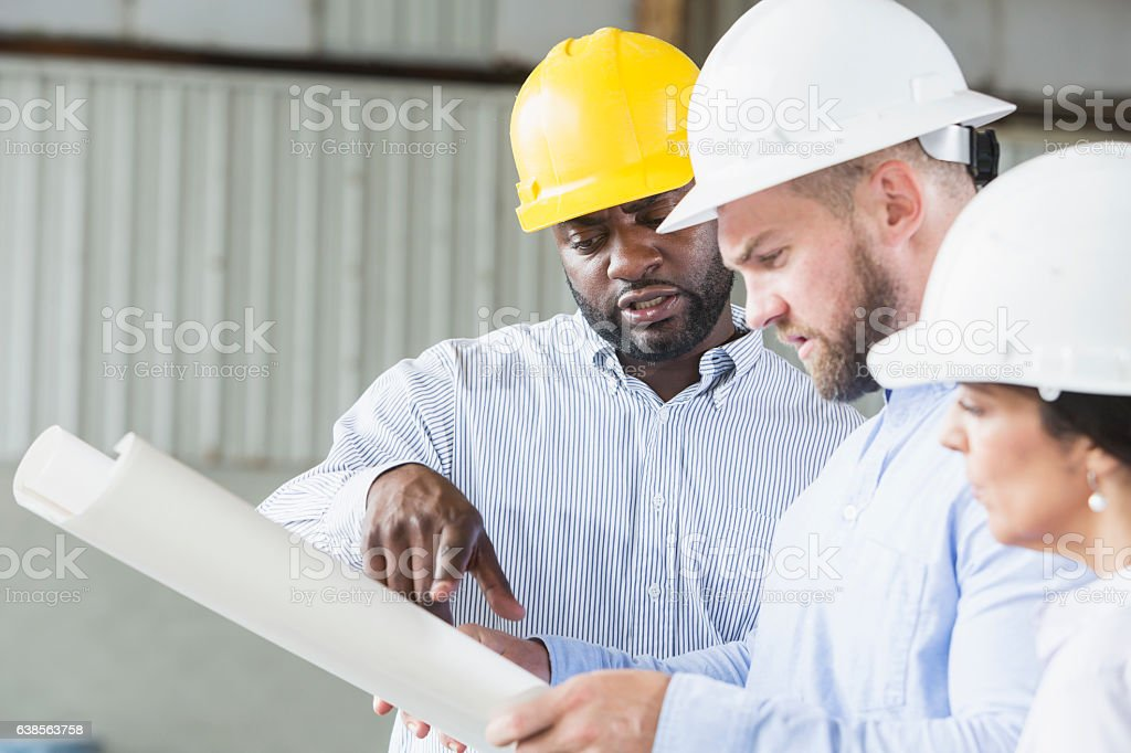 Multi-ethnic workers wearing hardhats looking at plans stock photo