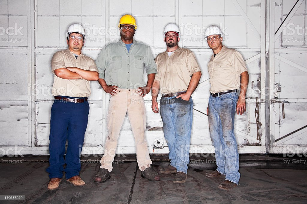 Multi-ethnic workers wearing hardhats stock photo