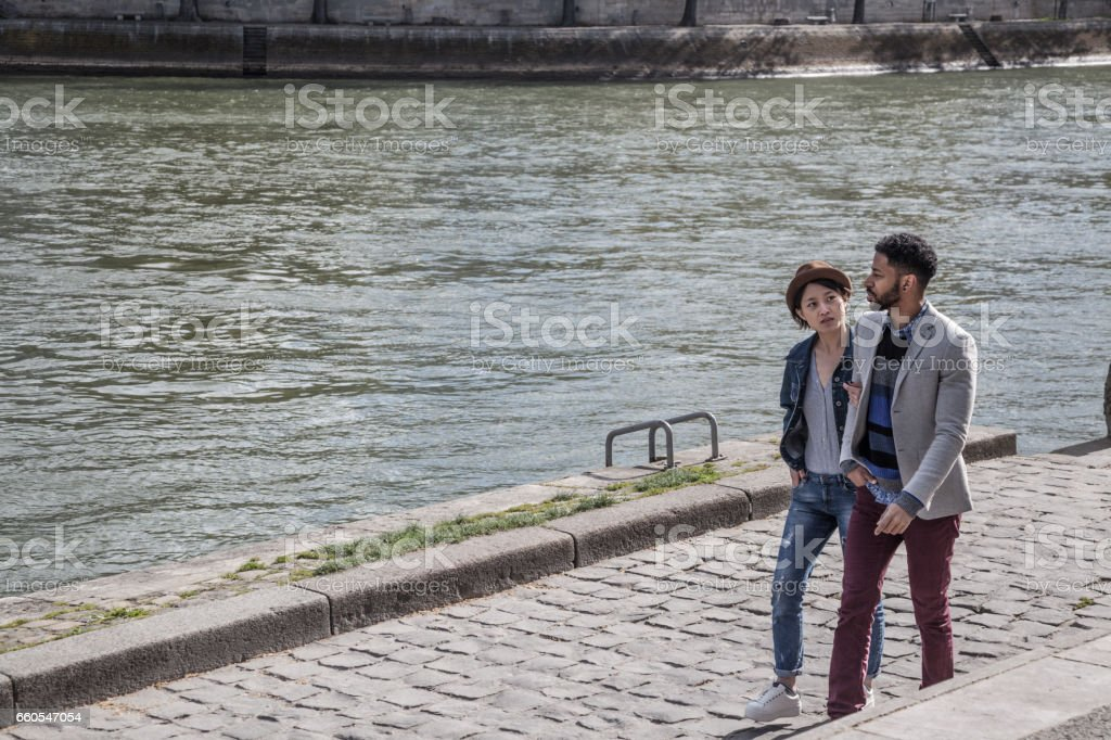 multi-ethnic young couple enjoy spring sunshine walking together on banks of the Seine Paris stock photo