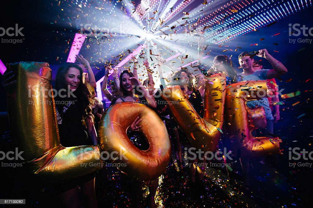 Multi-ethnic young friends celebrating a night club party with ballons stock photo