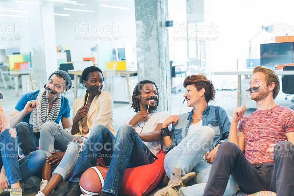 Multi-ethnic Young People Celebrating Movember In Their Office. stock photo