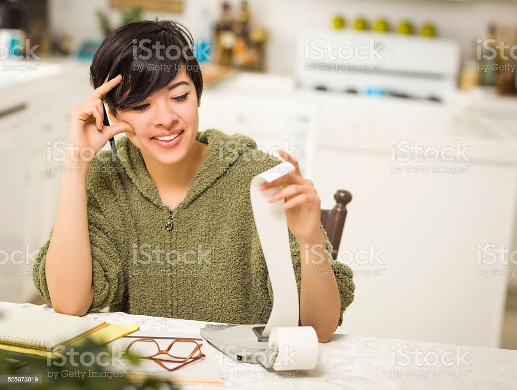 Multi-ethnic Young Woman Smiling Over Financial Calculations stock photo