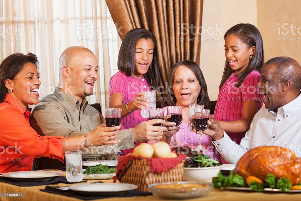 Multi-generation African American family gathering for holiday dinner stock photo