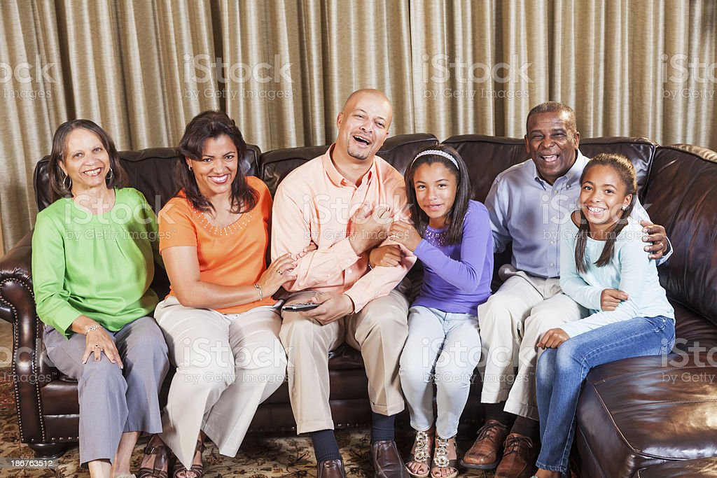 Multi-generation African American family sitting on couch laughing stock photo