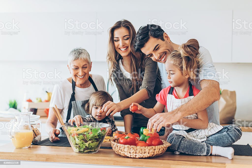 Multi-generation family cooking stock photo