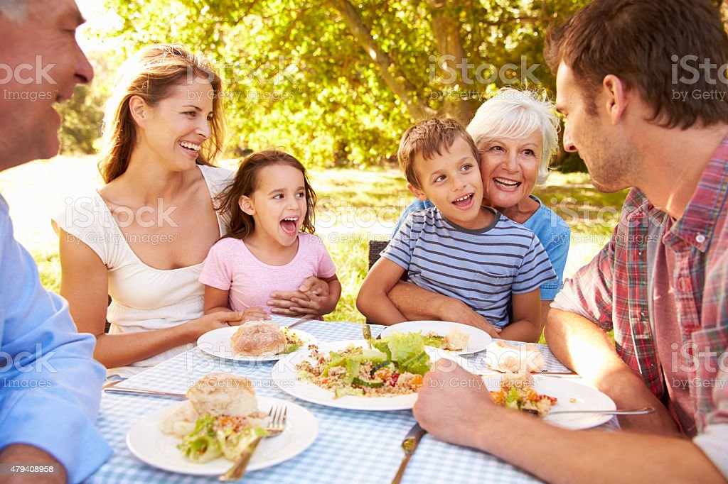 Multi-generation family eating together outdoors stock photo