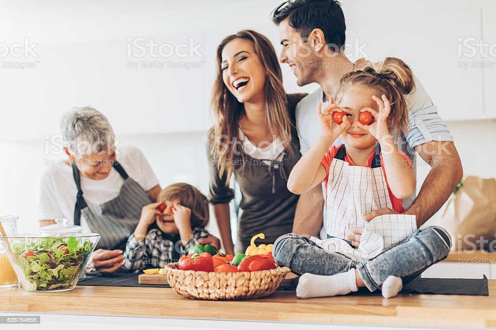 Multi-generation family having fun in the kitchen stock photo