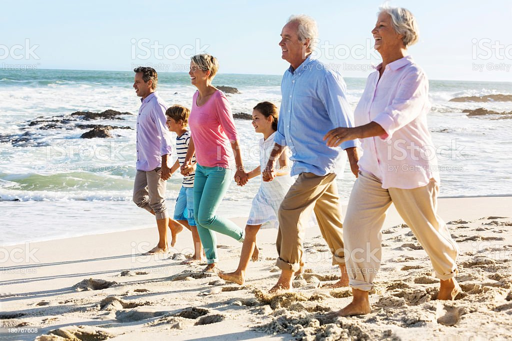 Multi-Generation Family Holding Hands While Walking On Beach royalty-free stock photo