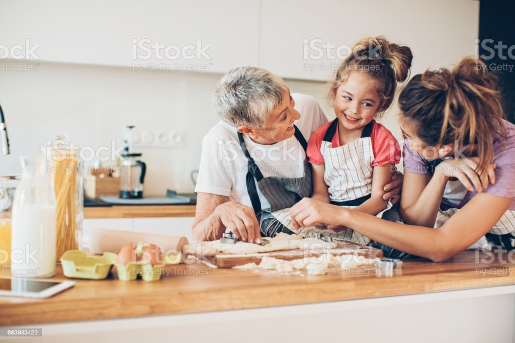 Three generations of women preparing cookies together in a domestic...