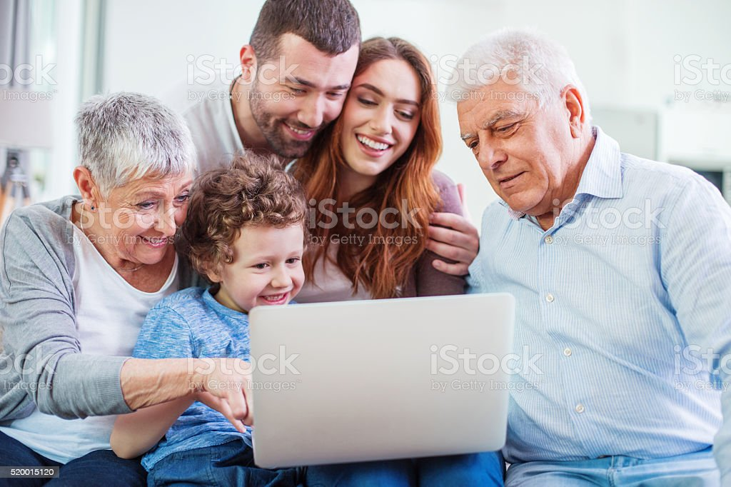 Multi-generation family looking at a laptop stock photo