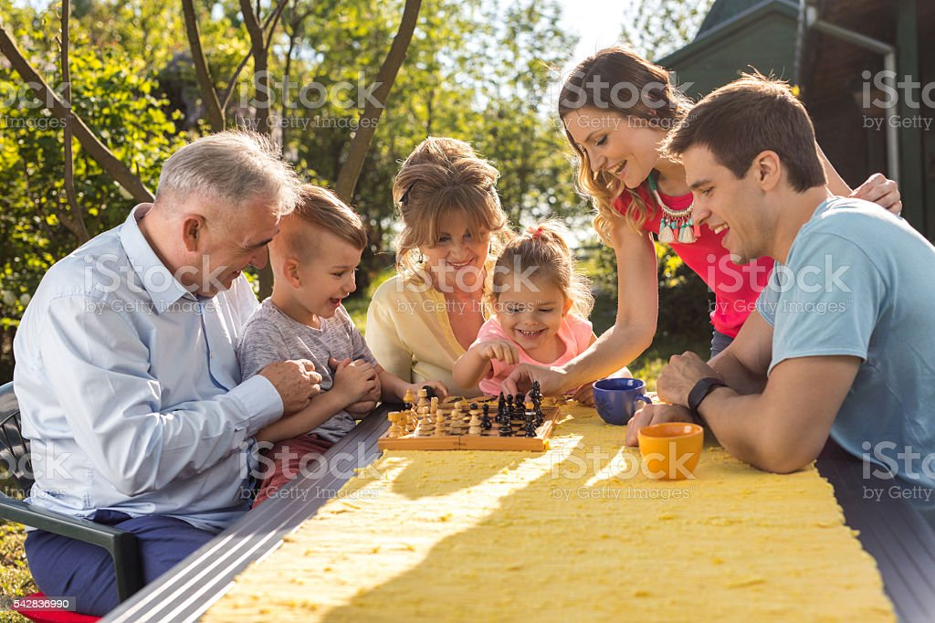 Multi-generation family playing chess in their backyard. stock photo