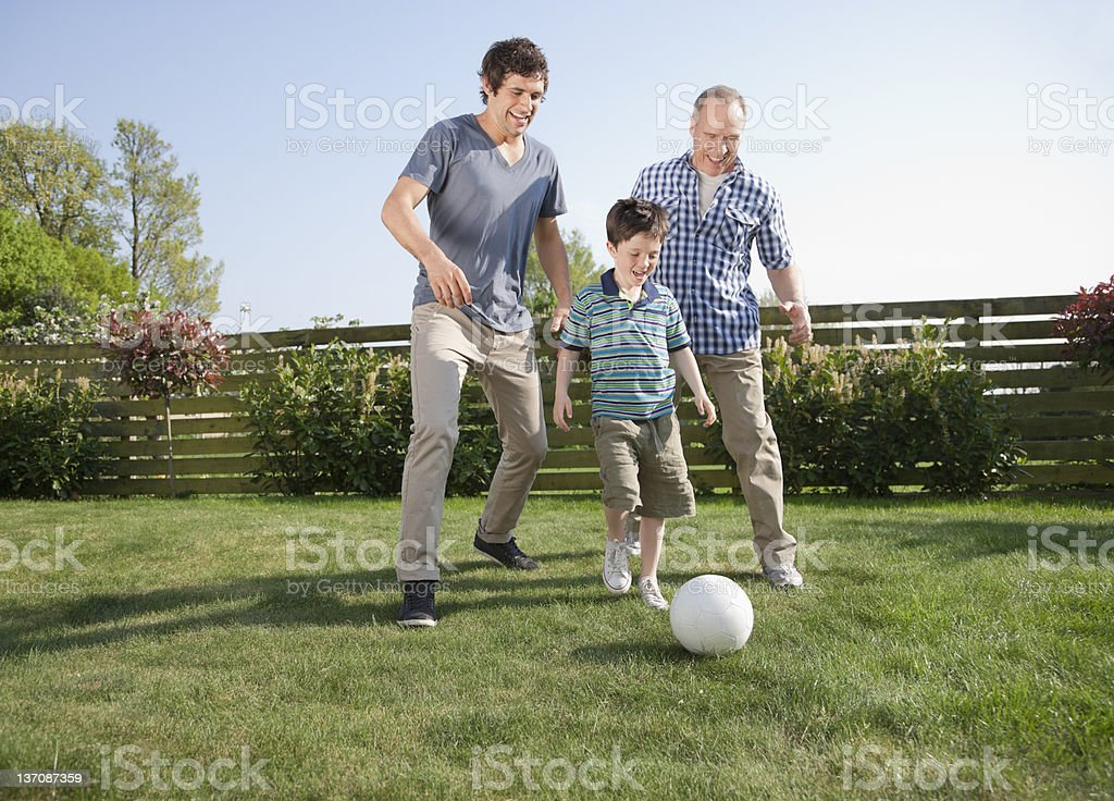 Multi-generation family playing soccer in backyard stock photo