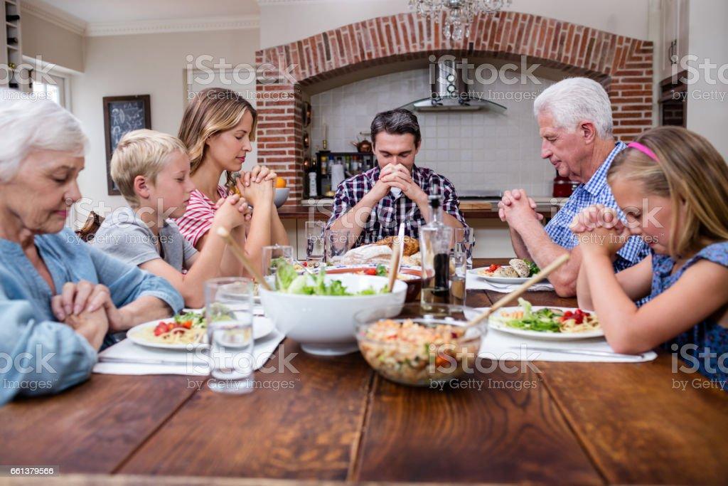 Multi-generation family praying before having meal stock photo