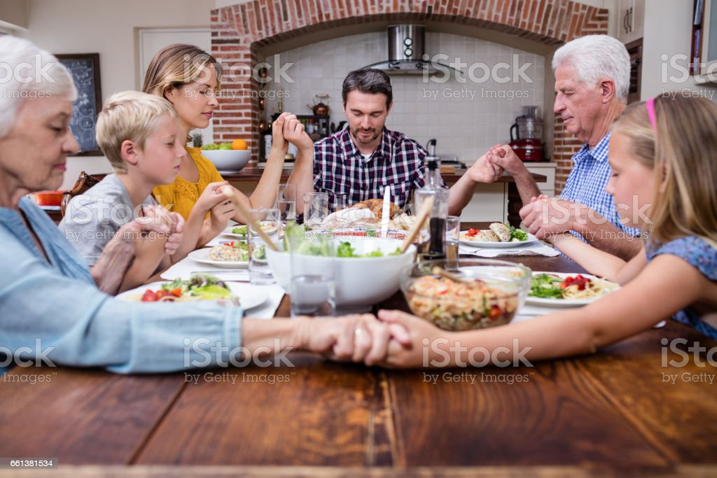 Multi-generation family praying before having meal stock photo