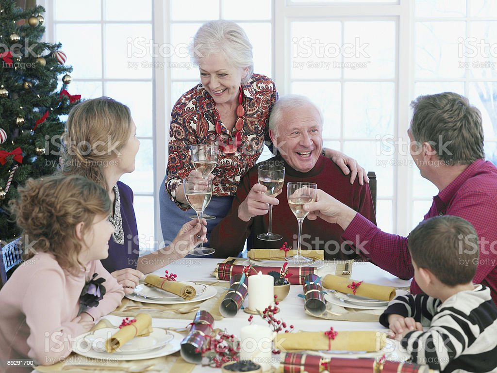 Multi-generation family toasting at Christmas dinner royalty-free stock photo