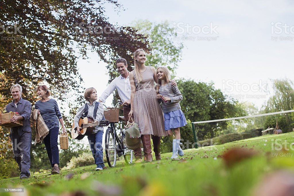 Multi-generation family with picnic baskets walking in park stock photo